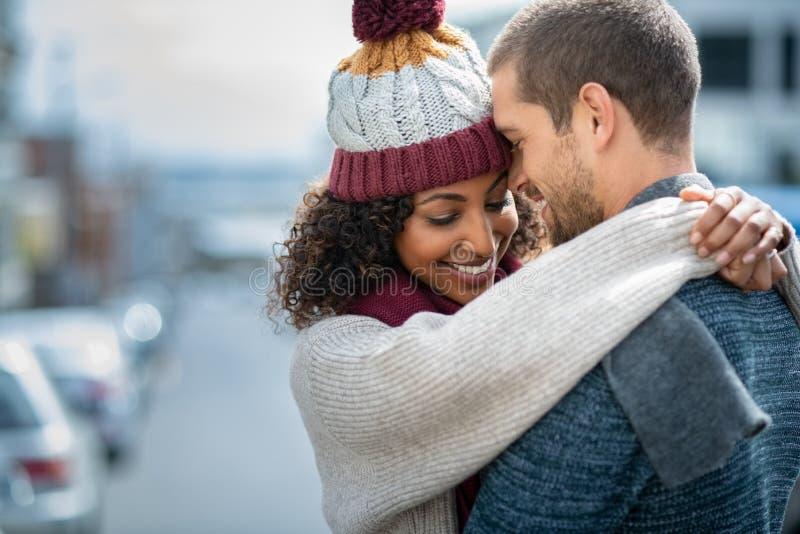 Förälskat omfamna för lyckliga par i vinter royaltyfri fotografi
