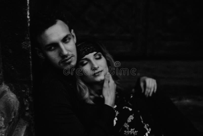Förälskat omfamna för stilfulla zigenska par i aftonstadsgata på royaltyfri bild