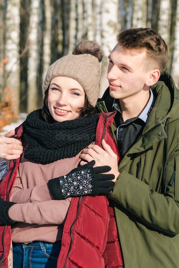 Förälskat parkerar krama för härliga unga par i på en klar solig vinterdag arkivbilder