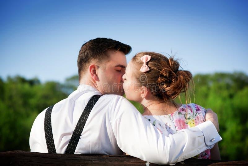Förälskat parkerar kyssa för barnpar på en bänk i sommar royaltyfri bild