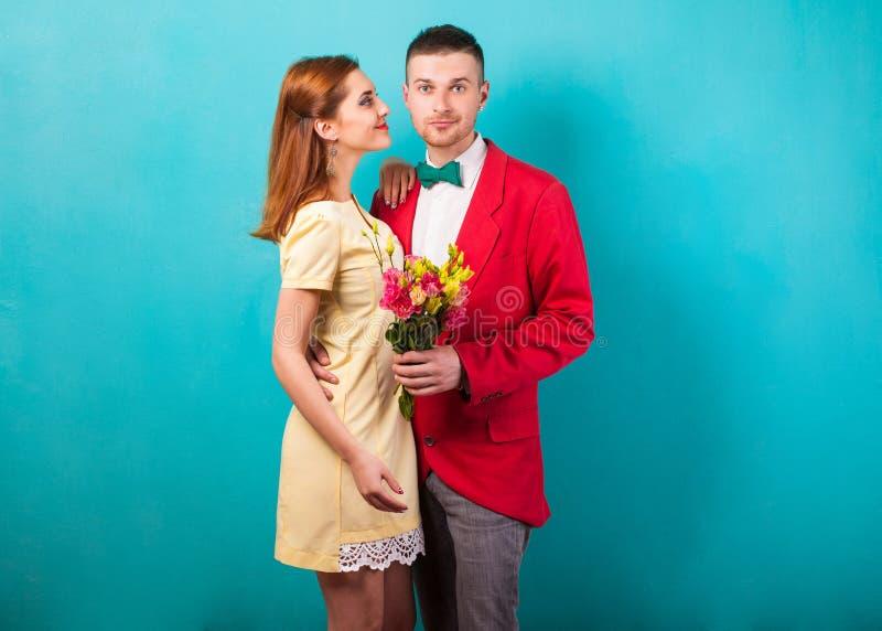 Förälskat posera för modehipsterpar på en guld- bakgrund Begreppet av dagen för St-valentin` s arkivfoton