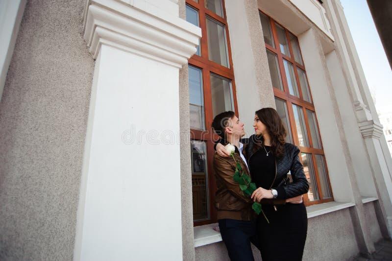 Förälskat posera för unga härliga par som är utomhus- i stad Ung kvinna som ler med hennes stiliga man arkivbilder