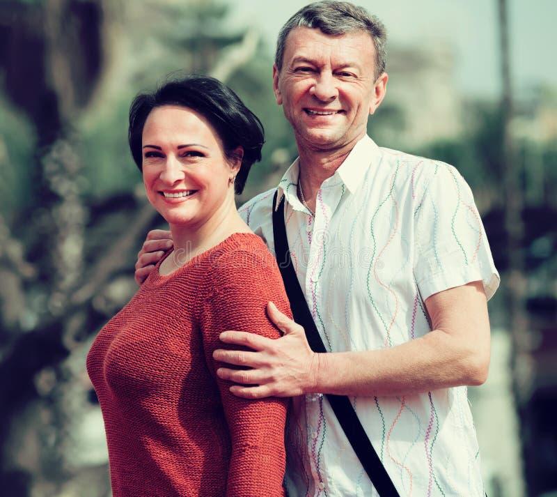 Förälskat posera för vuxna par utomhus tillsammans fotografering för bildbyråer