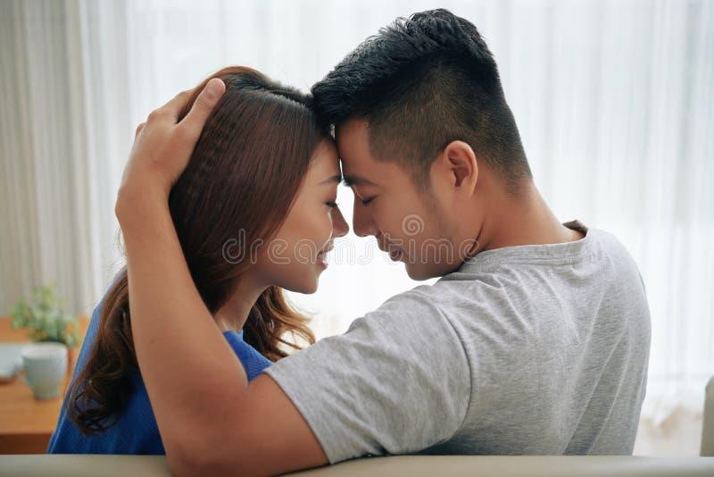 Förälskat sammanträde för härliga nära par på soffan arkivbilder