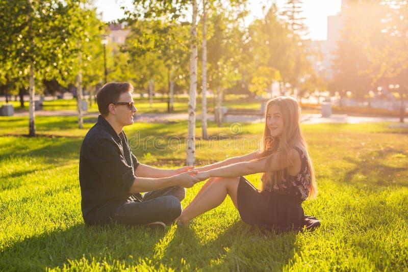 Förälskat sammanträde för par på gräset Förälskelse-, förhållande-, kamratskap- och fritidbegrepp arkivbild