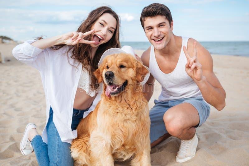 Förälskat sammanträde för unga stilfulla härliga par som spelar med hunden arkivfoto