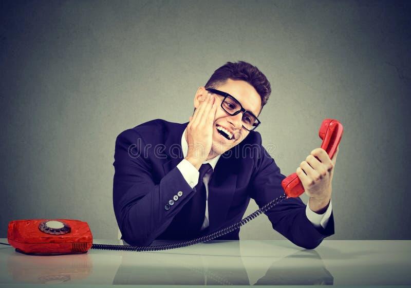 Förälskat samtal för ung rolig man på en telefon royaltyfri bild