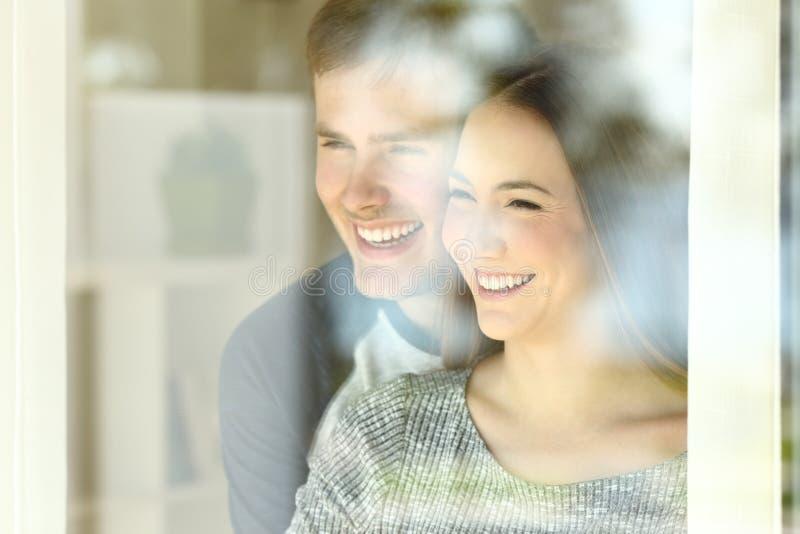 Förälskat se för par till och med ett fönster fotografering för bildbyråer