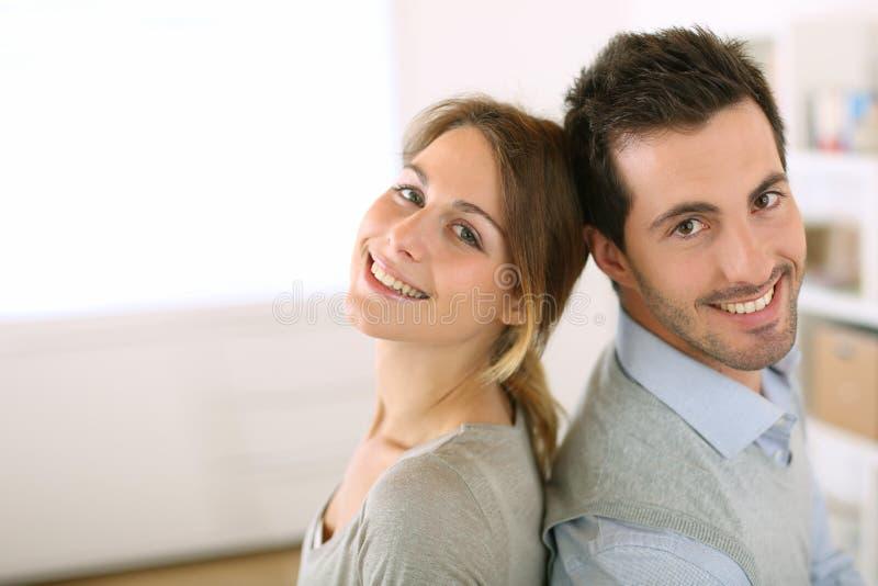 Förälskat sitta för lyckliga par tillsammans hemma arkivfoto