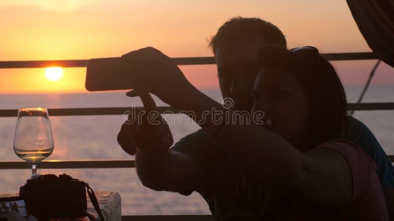 Förälskat tagande selfiefoto för unga lyckliga par med mobiltelefonen i strandkafé under härlig solnedgång- och drickavit royaltyfri foto