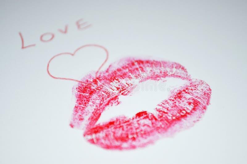 `-Förälskelse` är skriftlig på papperet med läppstiftkyssen royaltyfri bild