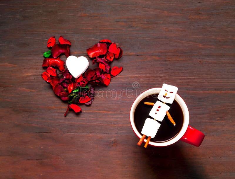 Förälskelse- eller valentindagbegrepp Stor röd kopp kaffe och marshmallowsnögubbe på träbakgrund fotografering för bildbyråer