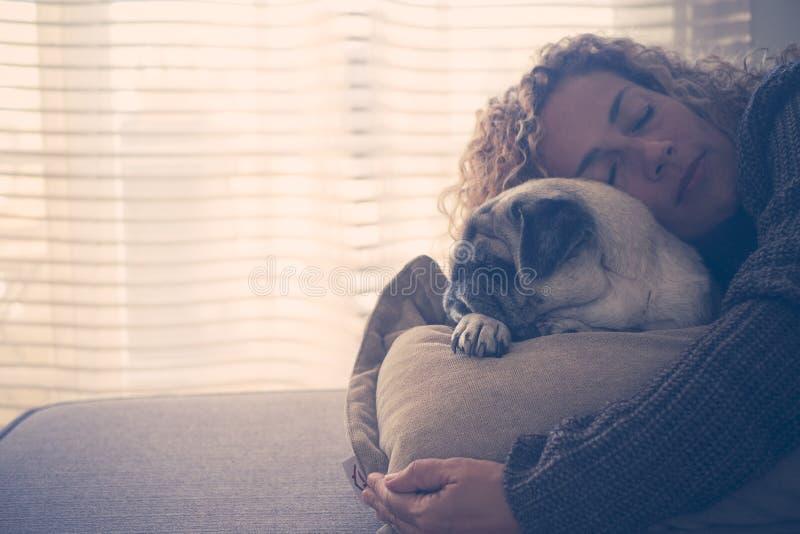 Förälskelse för folk och hundkapplöpning med den härliga caucasan vuxna kvinnan som sover med bästa vänmops på den hemmastadda so royaltyfria bilder