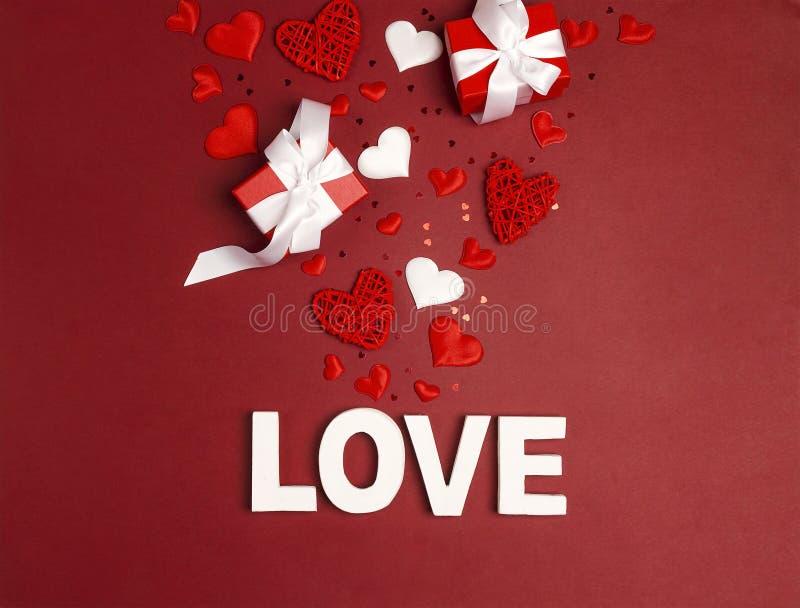 Förälskelse för ord för bakgrund för St-valentindag, gåvor och dekorativa hjärtor på rött royaltyfri foto