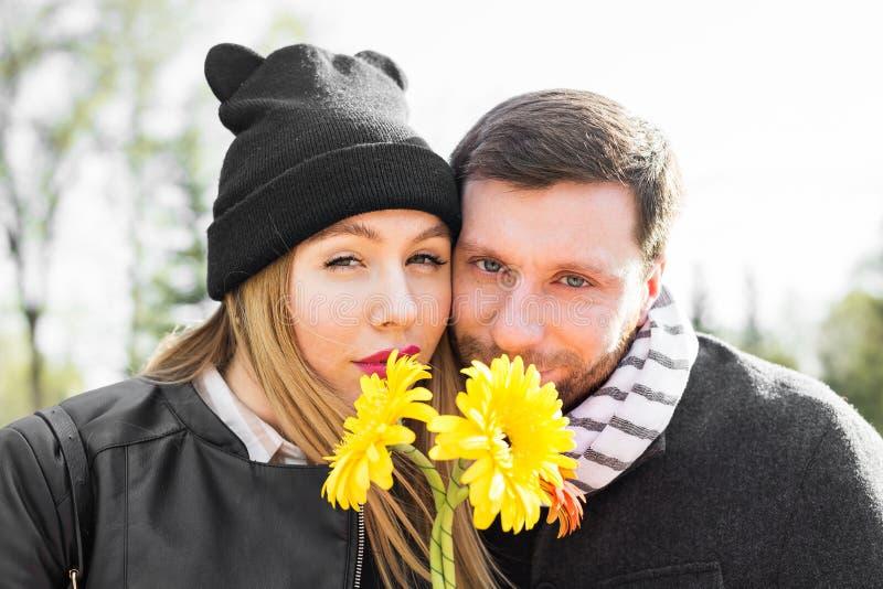 Förälskelse-, förhållande-, familj- och folkbegrepp - par med buketten av gerberas i höst parkerar fotografering för bildbyråer