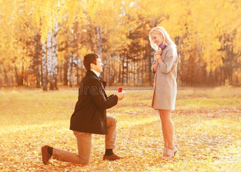 Förälskelse, förhållanden, kopplings- och bröllopbegreppet - den knäföll mannen föreslår en kvinna för att att gifta sig, röd ask royaltyfri fotografi