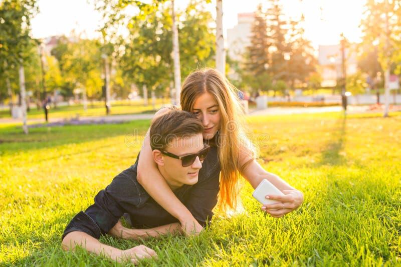 Förälskelse, folk och teknologibegrepp - lyckligt tonårs- par som ligger på gräs och tar selfie på smartphonen på sommar royaltyfria foton