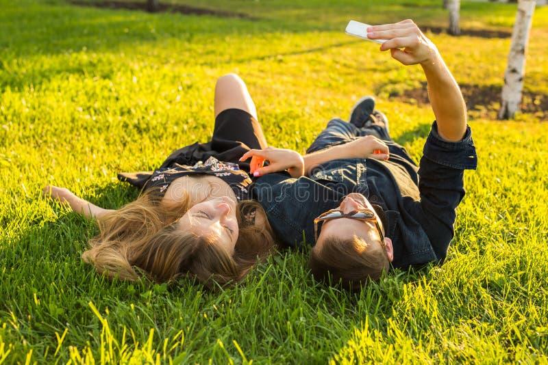 Förälskelse, folk och teknologibegrepp - lyckligt tonårs- par som ligger på gräs och tar selfie på smartphonen på sommar arkivbild