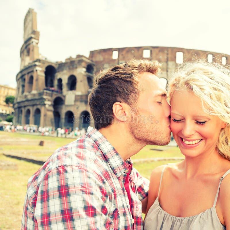 Förälskelse - kyssande gyckel för par i Rome vid Colosseum royaltyfri fotografi