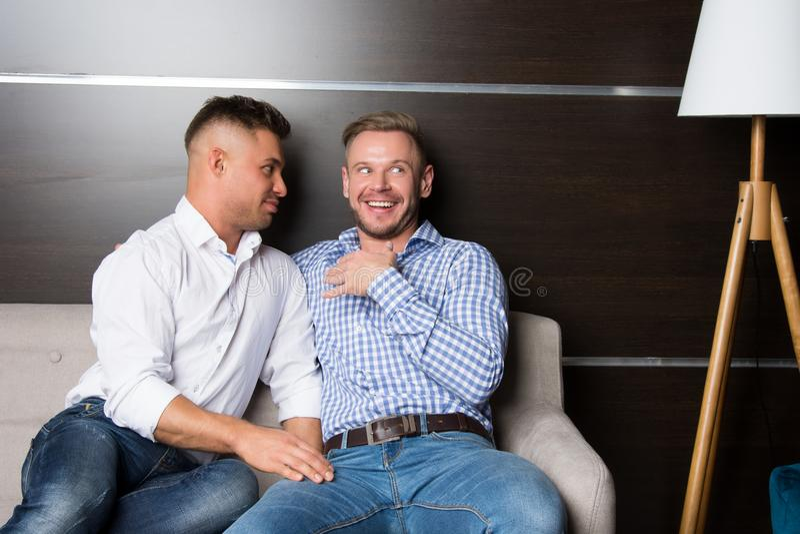 Förälskelse och förhållanden Två lyckliga grabbar tillsammans på soffan royaltyfri fotografi