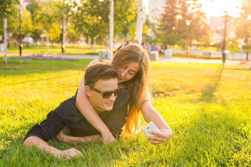 Förälskelse- och folkbegrepp - lyckligt tonårs- par som ligger på gräs och tar selfie på smartphonen på sommar fotografering för bildbyråer