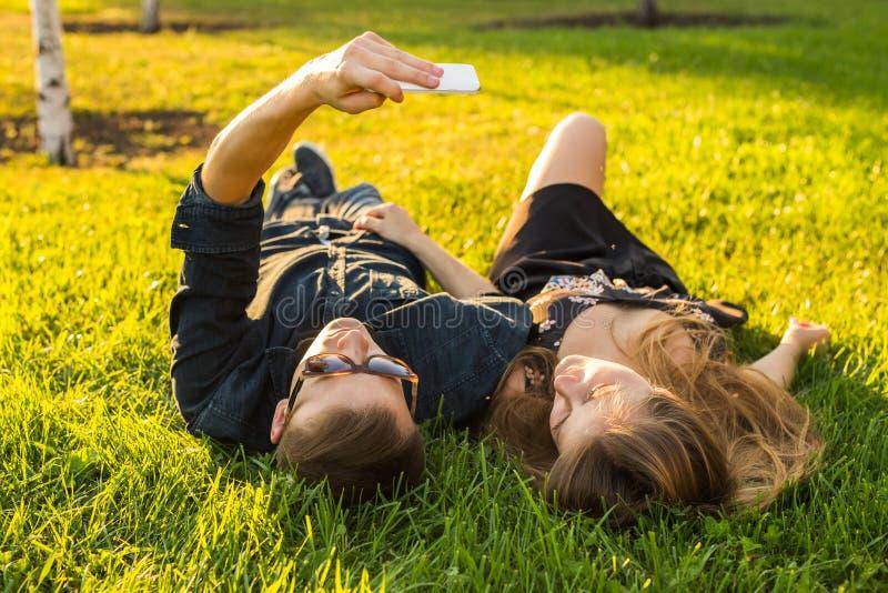 Förälskelse- och folkbegrepp - lyckligt tonårs- par som ligger på gräs och tar selfie på smartphonen på sommar arkivfoto