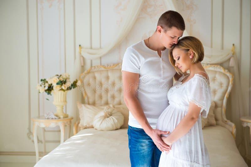Förälskelse och lycklig havandeskap Försiktiga härliga gravida par nära tyllgardiner arkivfoto