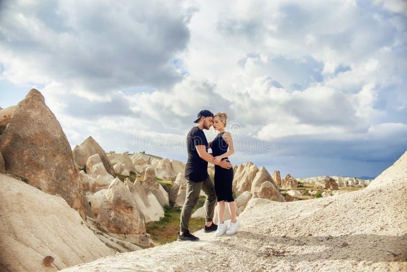 Förälskelse och sinnesrörelser som älskar par som vilar i Turkiet Det förälskade östliga paret i bergen av Cappadocia kramar och  arkivfoto