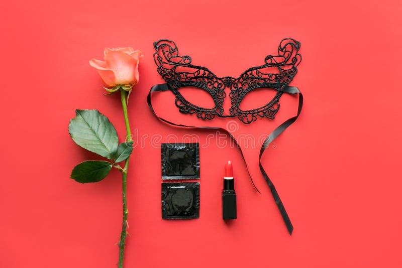 Förälskelse passion, könsbestämmer den romanska lägenheten lägger, falskt upp med den röda rosen, svart snör åt karnevalmaskering arkivfoton