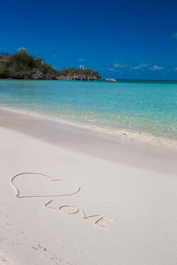 Förälskelse som är skriftlig på vit sand för tropisk strand royaltyfria bilder