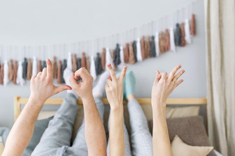 Förälskelse - som göras av fingrar av de älska paren Det härliga paret lägger i säng fotografering för bildbyråer