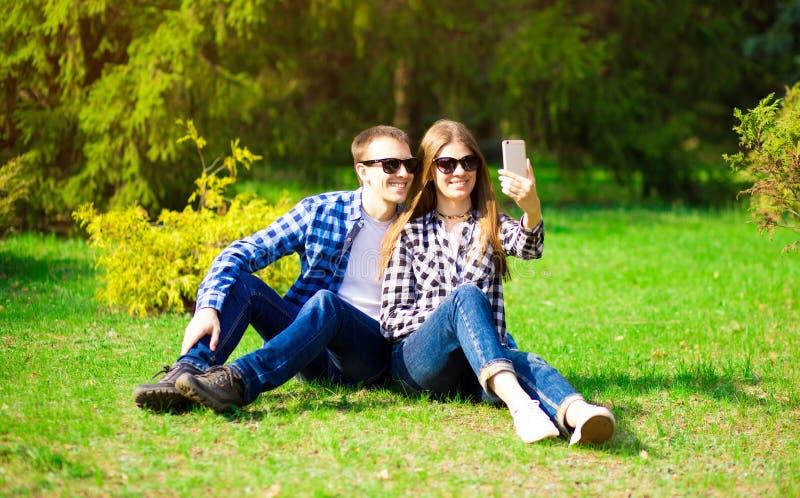 Förälskelse-, teknologi-, förhållande-, familj- och folkbegrepp - lyckliga le unga par som tar selfie i sommar, parkerar royaltyfri fotografi