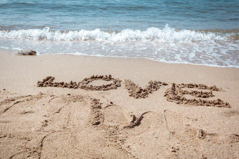 Förälskelse text på sand på stranden, manet bakom fotografering för bildbyråer