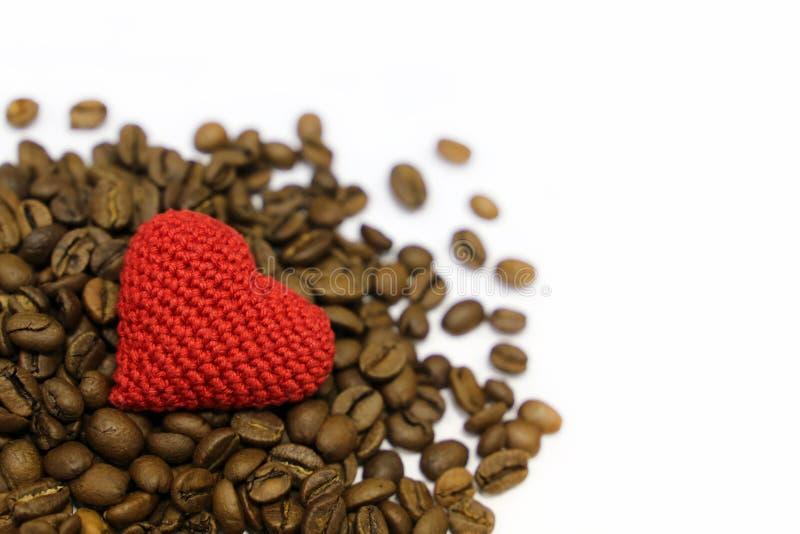 Förälskelse till kaffe, valentinhjärta och grillade kaffebönor som isoleras på vit bakgrund royaltyfri bild