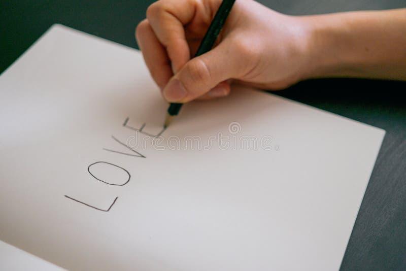 Förälskelsebegreppet - räcka handstilförälskelse på boken royaltyfria bilder
