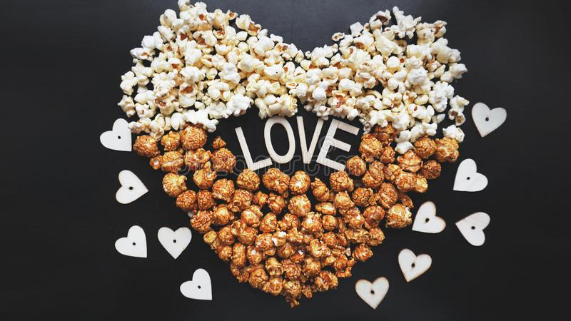 Förälskelsebiobegrepp av popcorn som ordnas i en hjärtaform Blandat popcorn royaltyfri bild