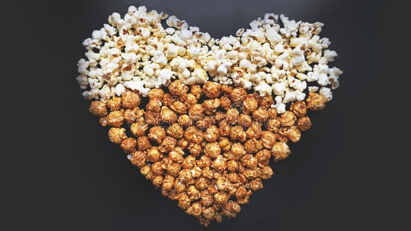 Förälskelsebiobegrepp av popcorn som ordnas i en hjärtaform Blandat popcorn royaltyfria foton