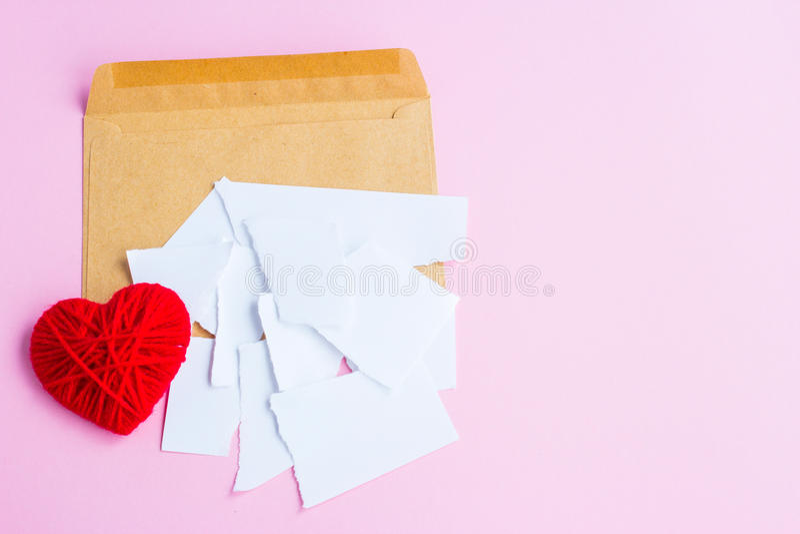 Förälskelsebokstav som är sönderriven med röda hjärtor arkivbild