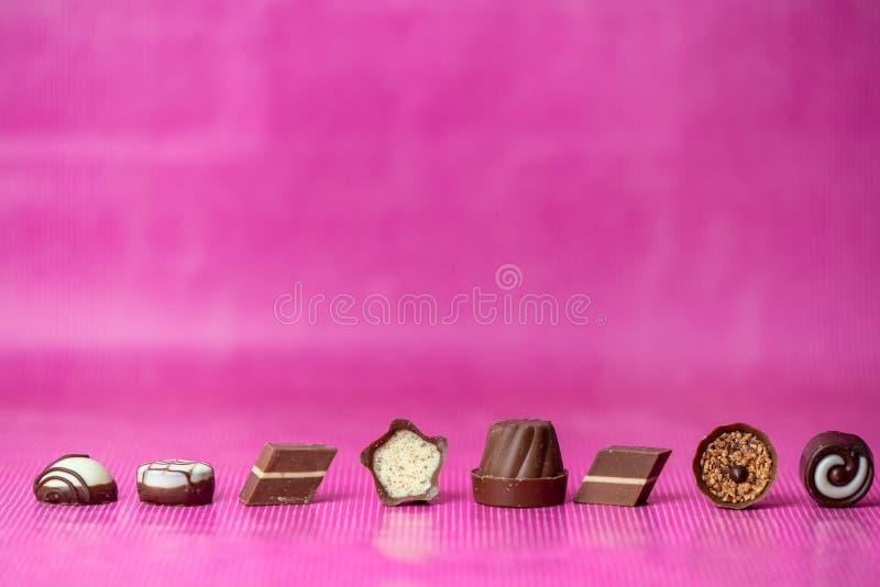 Förälskelsechoklad - söta choklader i en linje på en rosa bakgrund royaltyfri foto