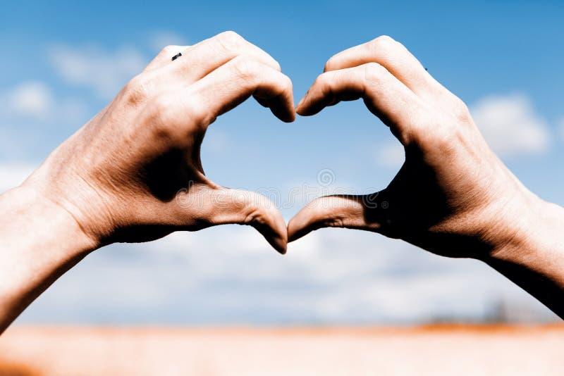Förälskelseformhänder - hjärta på gult fält och blå himmel arkivfoton