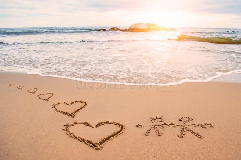 Förälskelsehjärtamålning på stranden royaltyfri bild