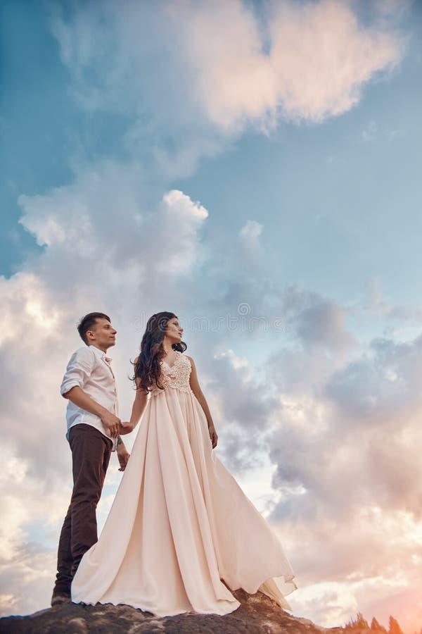 Förälskelsekyss och förälskade par för kramar på solnedgången i aftonsolen, en gå till och med bergen och kullar Sinnligt och för arkivfoton