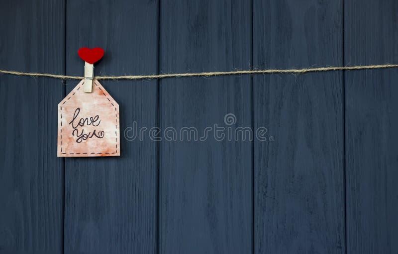 Förälskelsemeddelande på dag för valentin` s med ord`-förälskelsen dig ` och rosa färghjärta handgjort Lekmanna- lägenhet vattenf fotografering för bildbyråer