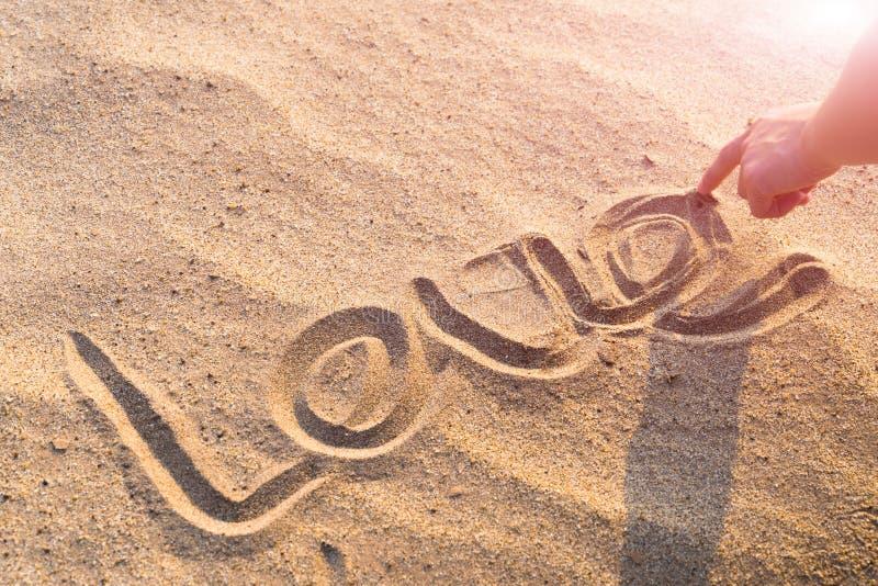 FÖRÄLSKELSEordhandstil på den vita sandnaturen på stranden Sommartur royaltyfri foto