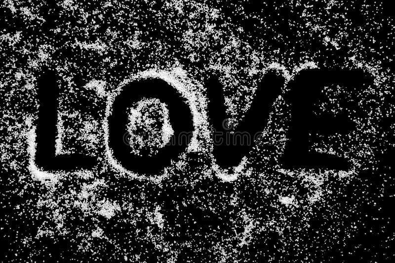 Förälskelseordsymbolet som drar vid fingret på vit, saltar pulver på svart brädebakgrund royaltyfria foton