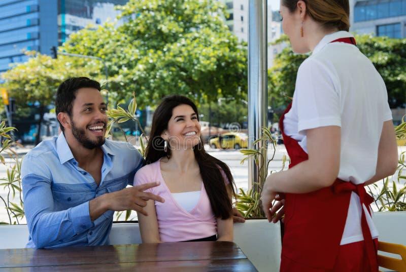 Förälskelsepar förlägger en beställning på en caucasian servitris royaltyfri bild