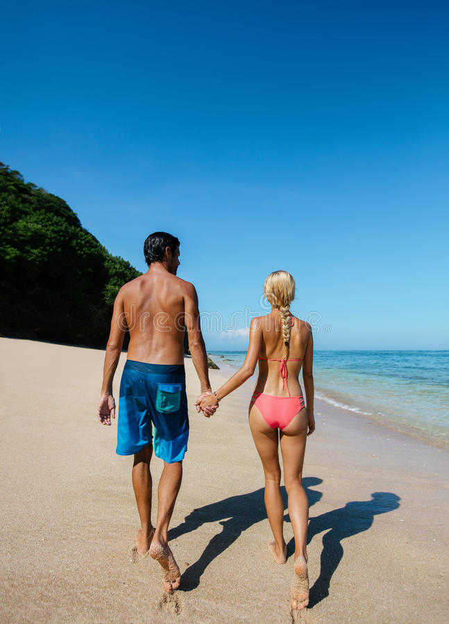 Förälskelsepar som promenerar den tropiska stranden arkivbilder