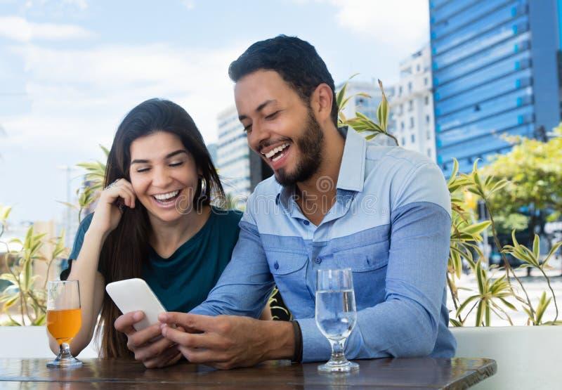 Förälskelsepar som ser telefonen på restaurangen royaltyfri foto