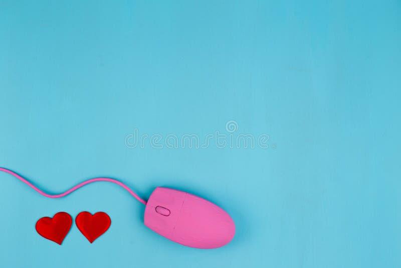 Förälskelsepratstund, online-datummärkning Rosa datormus med rött tyg honom arkivbild