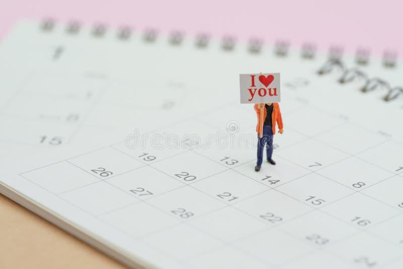 Förälskelsesymbolet eller romans av valentins dagbegreppet, det miniatyrtecknet för folkgentlemaninnehavet med meddelandet älskar royaltyfri foto